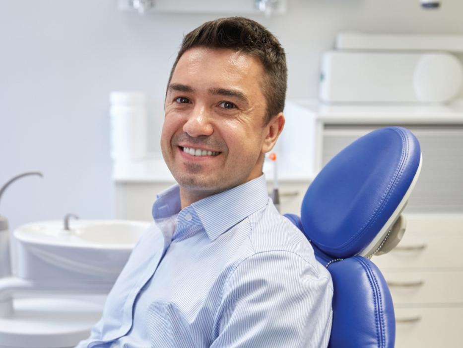 man smiling sitting in a dental chair