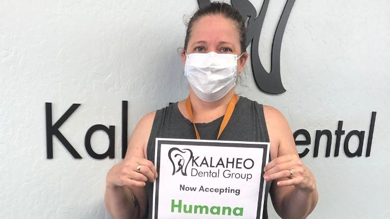 woman smiling and holding a humana sign